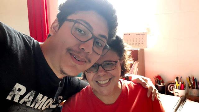 Mulher e rapaz, ambos de óculos, abraçados, fazem selfie