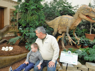 a man and boy sit together on a stone wall with dinosaur statues and plants behind them