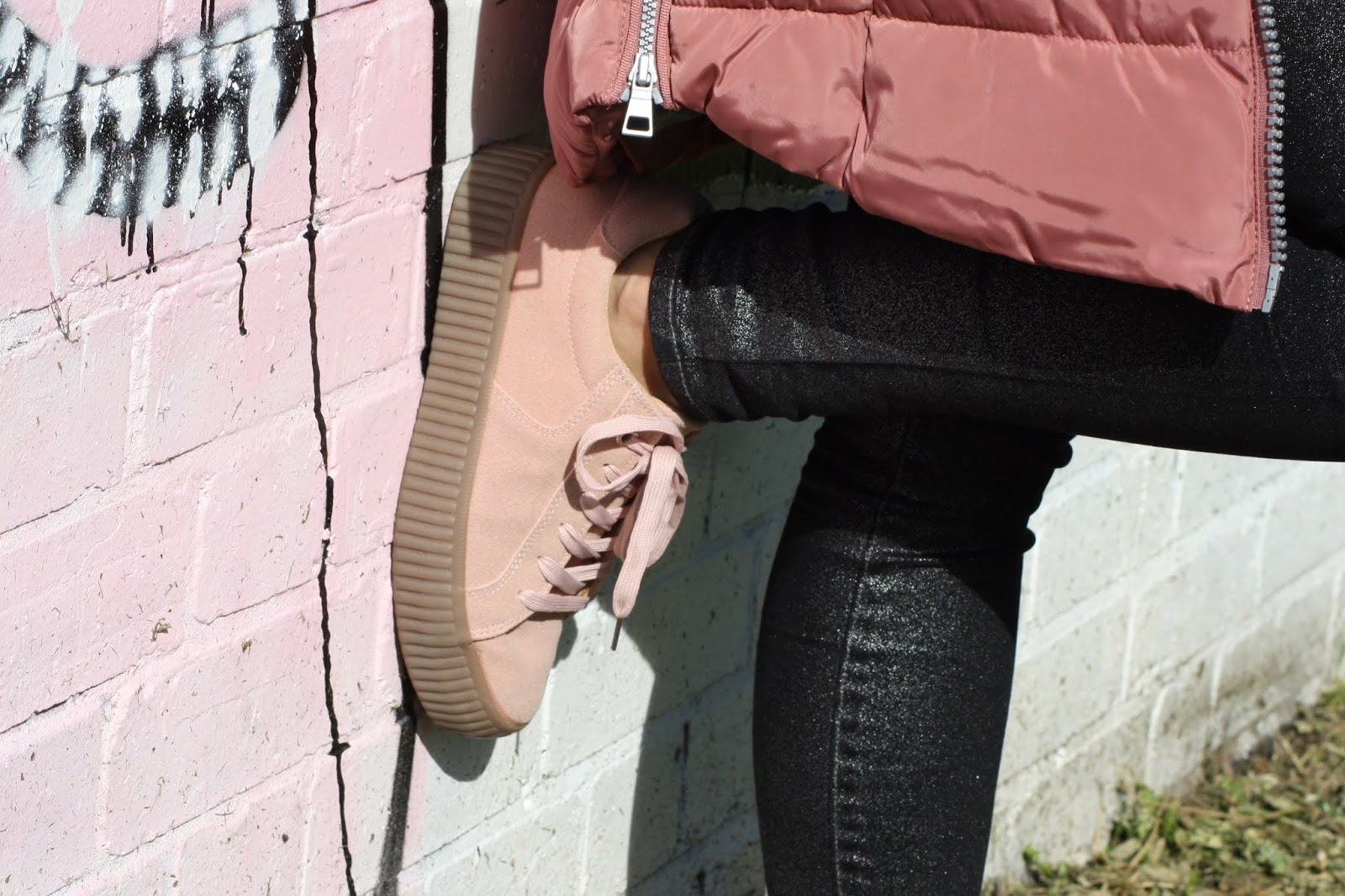 A close up of Abbey's pink thick-soled lace up trainers, leaning against a graffiti wall