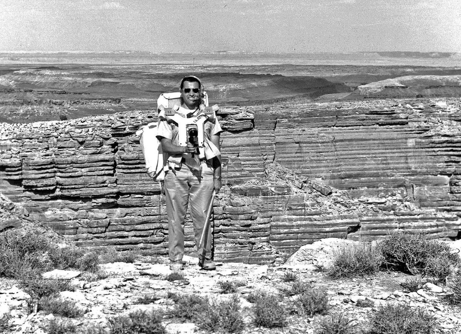 The Apollo 17 astronaut Harrison Schmitt stands on the edge of an erosional canyon that was used to simulate the large Hadley Rille at the Apollo 15 landing site. Schmitt was originally part of the Apollo 15 backup crew, and later slated to fly in Apollo 18. When that mission was canceled, Schmitt was moved up to Apollo 17 due to his previous work and studies as a professional geologist.