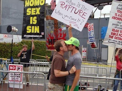 Funny Christian gay homosexual protest signs - where is the rapture when you need it? Two men kissing in front of a group of Christian protestors