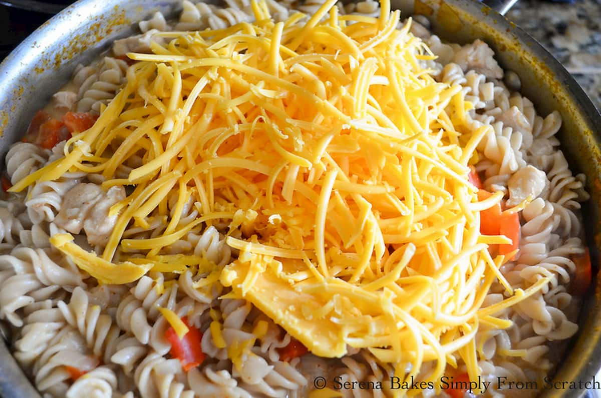 Shredded Cheese added to Cooked Chicken and Pasta in a stainless steel pan.