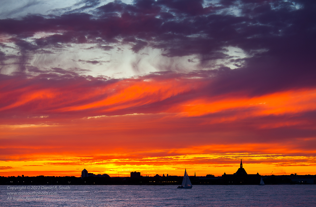 a photo of a sailboat in new york harbor at sunset