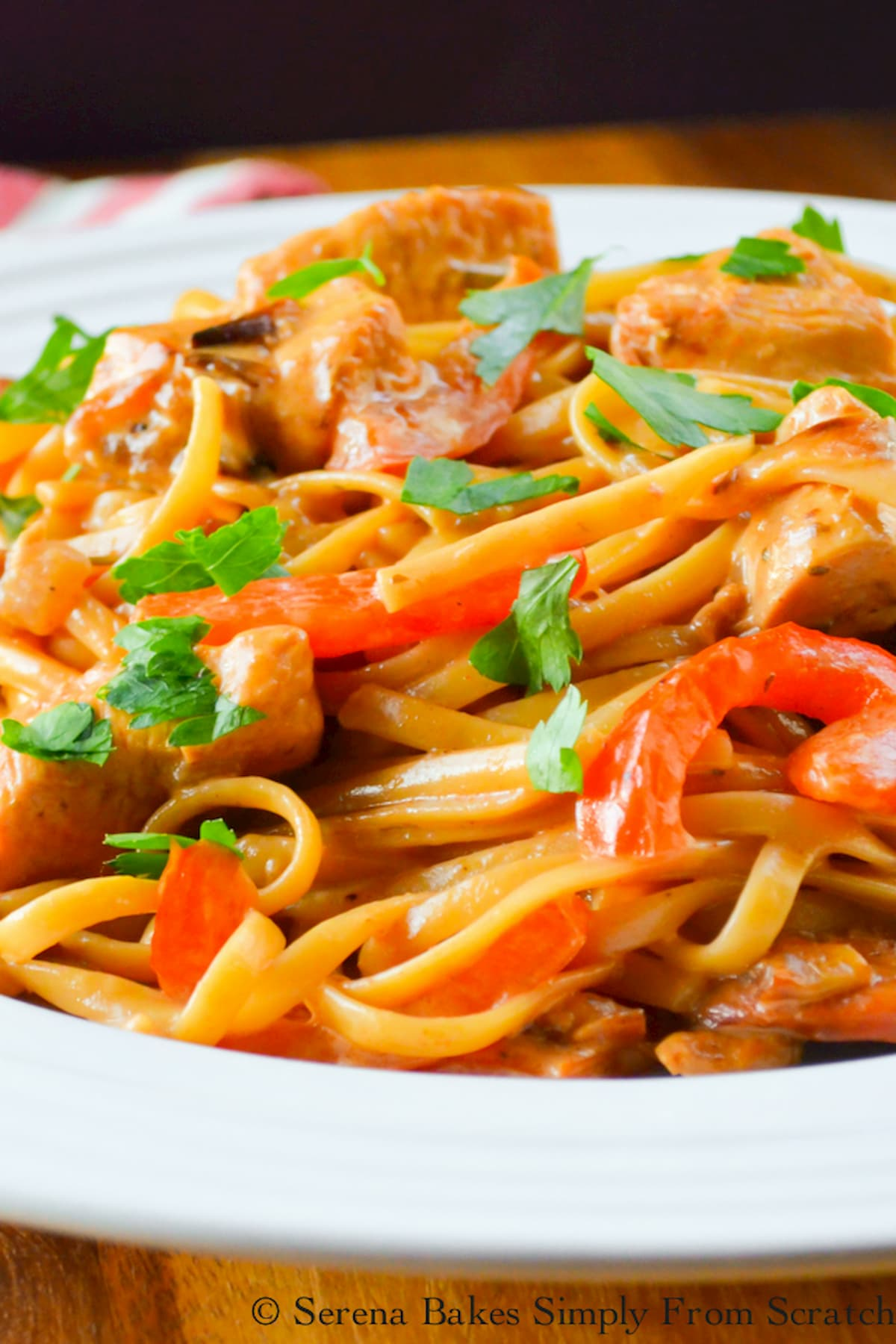 One Pot Cajun Chicken Pasta in a white pasta bowl sprinkled with parsley picture tooken of pasta from the side.