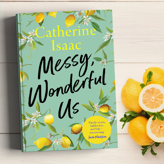 Book to the left hand side. Cover is a pastel green with flowers around the edges and lemon trees. Lemons placed to the right hand side, white wooden flooring background