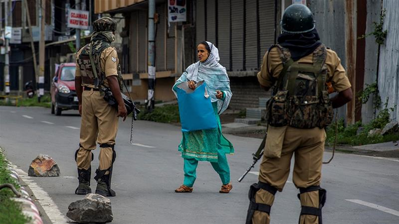 Indian forces stop a Kashmiri woman going to a hospital amid restrictions in Srinagar