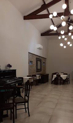 Piano e mesas do espaço de eventos da Casa MIndela