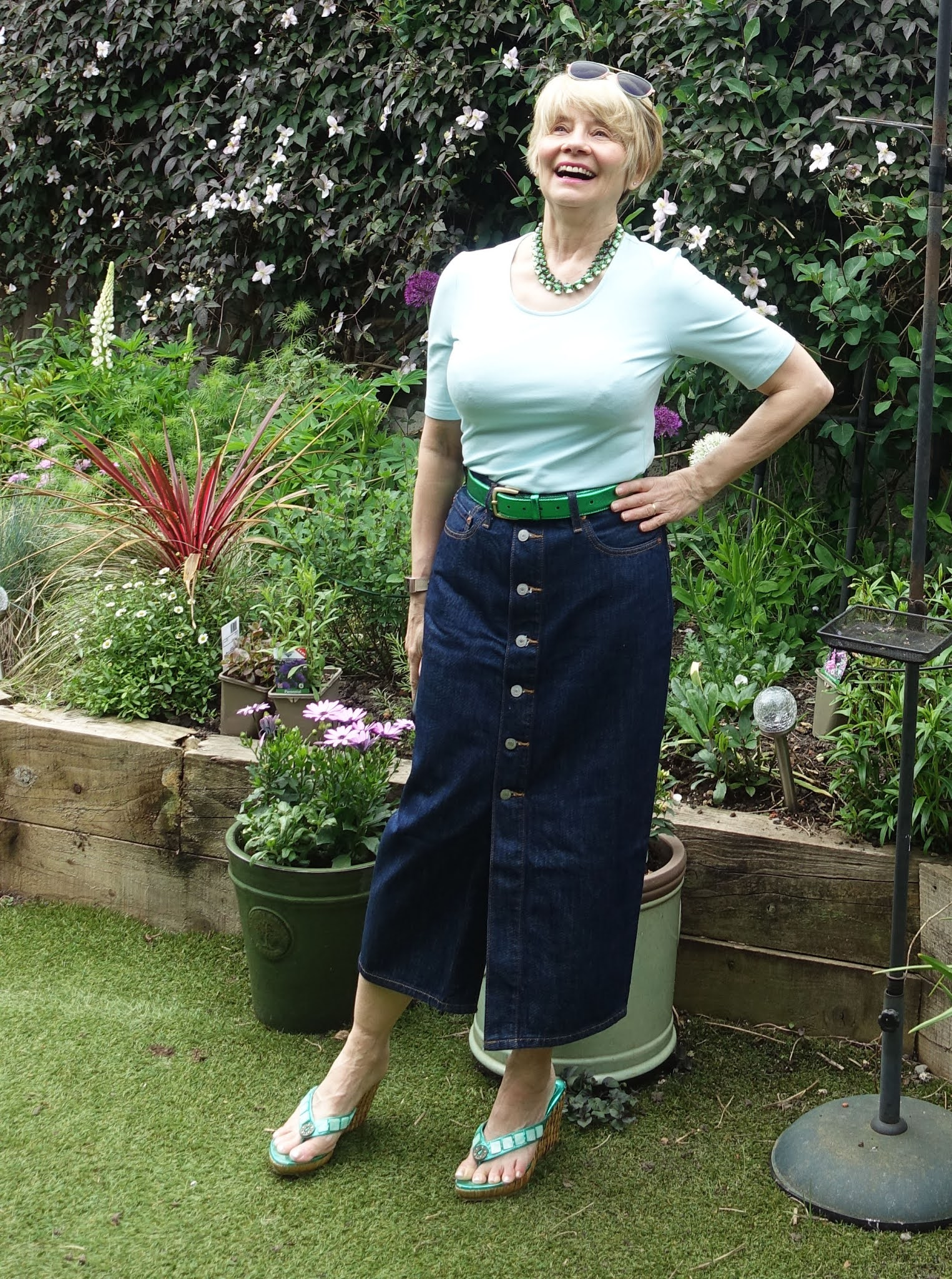 Laughing shot of Gail Hanlon from Is This Mutton in denin midi skirt and light green top with emerald wedges