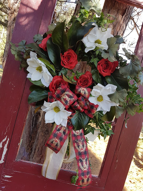 white magnolia wreath on red door