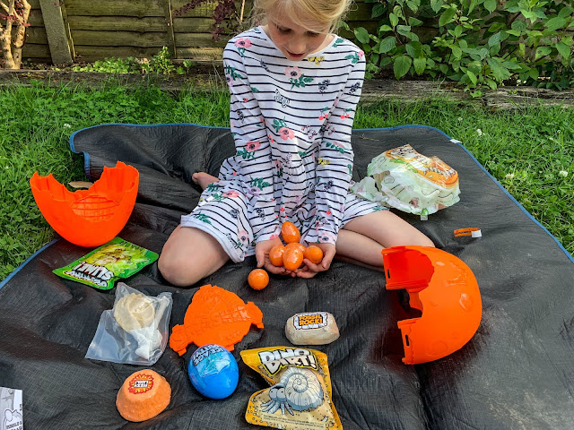 A girl showing 6 orange Smashers eggs and surrounded by the contents of the Epic Dino Egg including the egg shell, ice age putty, fizzy lava, glowing slime, dino dirt and fossil rock
