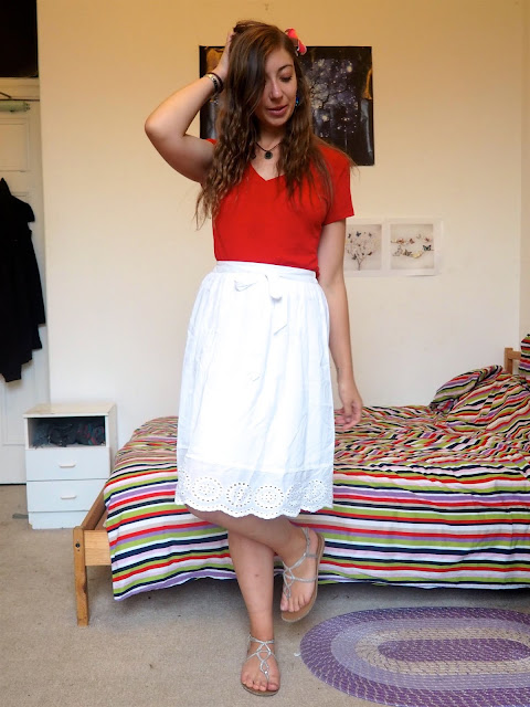 Moana inspired Disneybound outfit of bright red top, long white skirt, silver sandals, blue stone jewellery & island flower clip