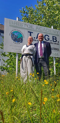 Glowing lady in TKD suit with smart dressed chap, standing in front of a sign that says 'Bristol Academy' on an overgrown lawn with lots of yellow flowers and pretty grass