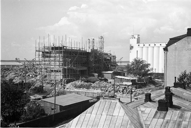 Mustavalkoinen kuva. Kuvassa näkymä kaupungista yli kattojen. Taustalla valkoinen viljavarasto ja rakenteilla oleva korkea rakennus.