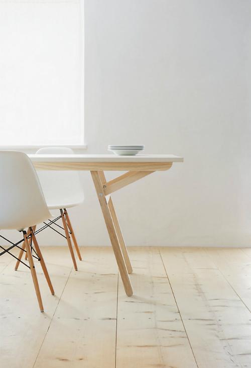 In einem Esszimmer steht ein Tisch aus hellem Holz und Stühlen. Tisch von Nils Holger Moormann