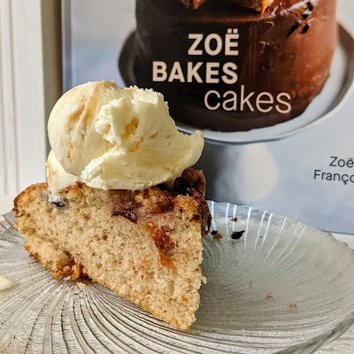 A slice of plum cake topped with ice cream. In the background is the cookbook the recipe comes from - Zoe Bakes Cakes