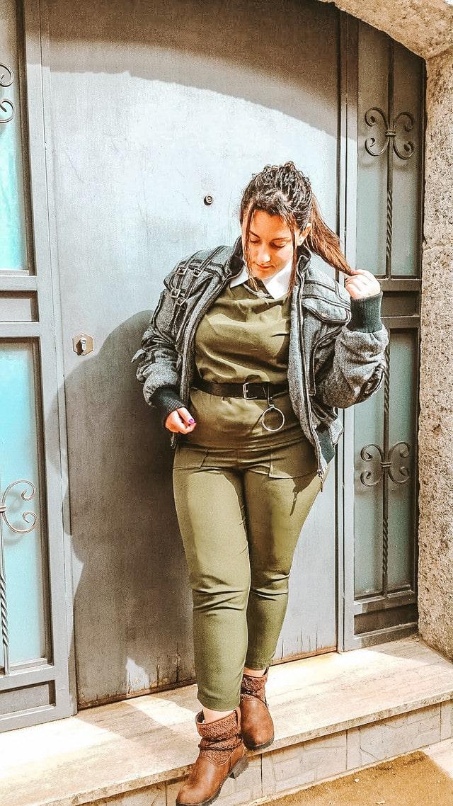 ragazza in piedi sulle scale con completo verde stivali e giacca