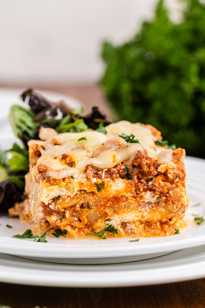 Close up photo of a serving of keto lasagna on a white plate with a salad.