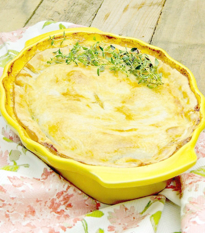 Salmon pot pie in a yellow casserole dish on a wooden table with floral towel.