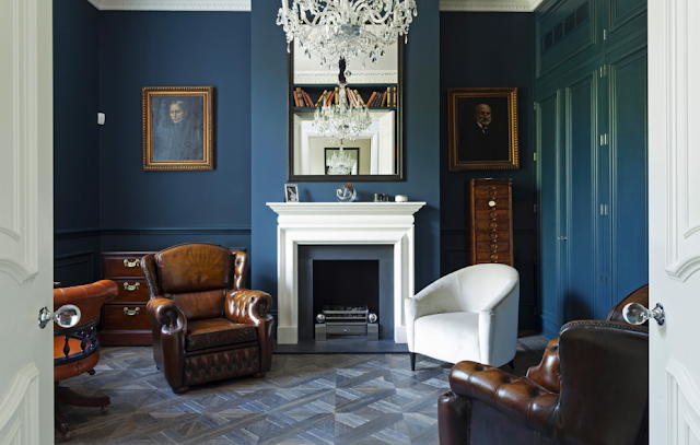Blue library in a suburban London home with leaher club chairs, carved crown moulding, parquet wood floors, decorative wall moulding and paneling
