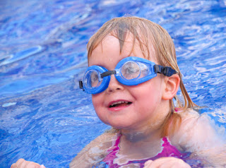 Image of a happy child in the swimming pool wearing google: Swim schools need communicating during tough times