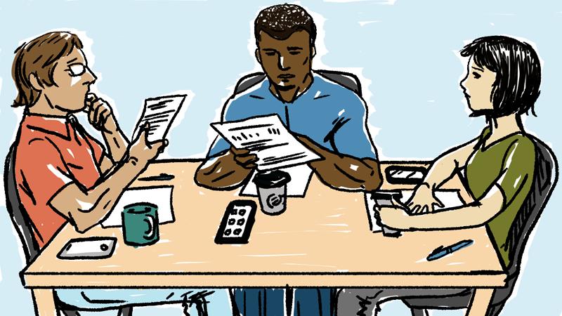 Три человека сидят за столом и читают договор