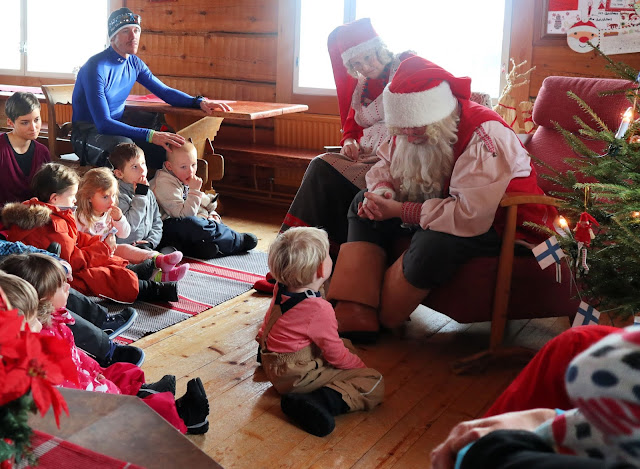Santa, seated in front of a small crowd of children, talking to a little boy at the front.
