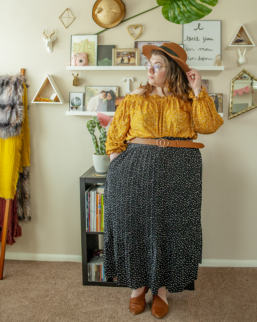 An outfit consisting of a brown panama hat, yellow micro floral off the shoulder blouse tucked into a white on back polka dot midi skirt and brown d'orsay flats.
