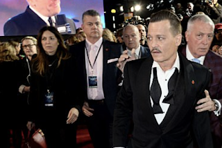 'Everyone thought he'd been drinking': Johnny Depp appears worse-for-wear as security guard seems to prop him up during red carpet arrival at Murder On The Orient Express premiere