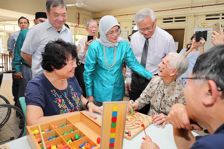 President Halimah Yacob chatting with St John's Home resident Tan Sing Choon, 93, and volunteer Anita Lin (left, in blue), 72, yesterday. Accompanying the President are Potong Pasir MP Sitoh Yi Pin (behind Madam Lin) and Mr Woon Wee Yim, the home's chairman.