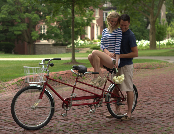 This engaged couple posing on the tandem bike holding flowers look happy.
