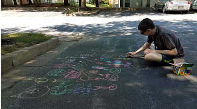 Image: Caucasian teen boy drawing with chalk on blacktop pavement in a rainbow of colors.
