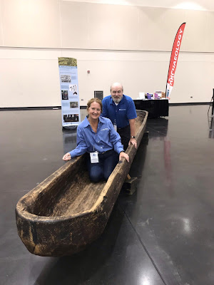 Large wooden dugout canoe with 2 people inside, also banners and tables in convention center