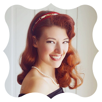 A caucasian woman with red hair in a vintage style smiling at the camera.