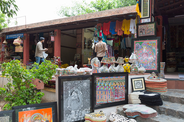People shopping and handicraft items for sale at Dilli Haat market in New Delhi India