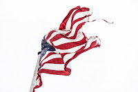 A tattered US Flag blows in the wind
