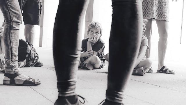 siedzący chłopiec, nogi innych ludzi