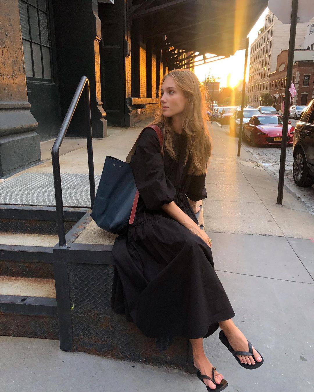 Easy Summer Outfit Instagram Inspiration — Scandinavian model Amalie Moosgaard Neilsen in a black puff sleeve midi dress and black flip flop sandals