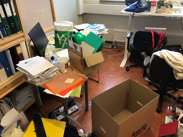 Toimistototavaraa kuten papereita ja laatikoita toimiston lattialla