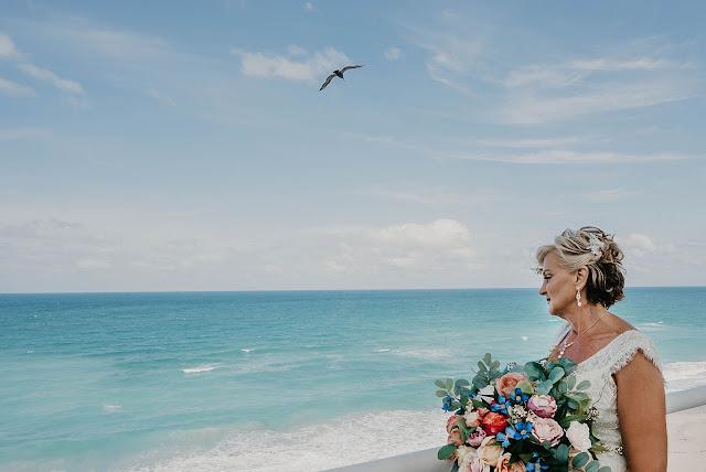 Bride looking at calm ocean water