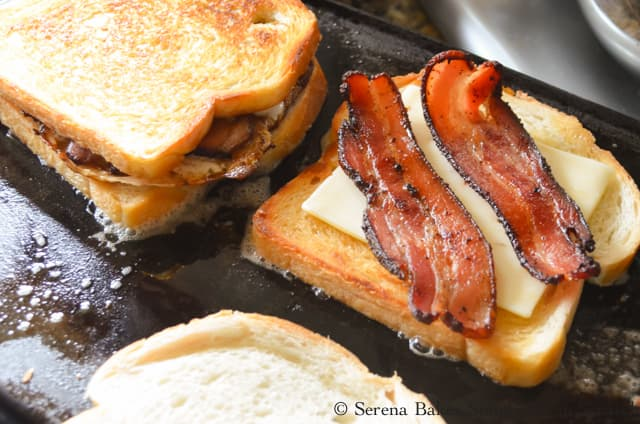 2 Slices of Bacon on top of cheese over grilled sourdough bread surrounded by 2 breakfast sandwiches.