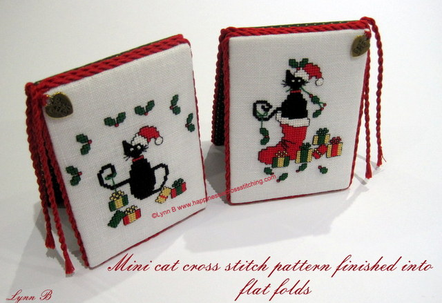 Cross stitch ornaments finished into flatfolds showing Mini Black Cats wearing a Santa hat with parcels and one black cat sitting in a christmas stocking.