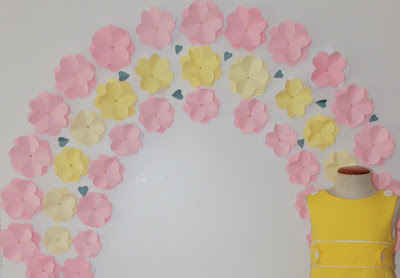 Arco con flores de cartulina para escaparate de primavera