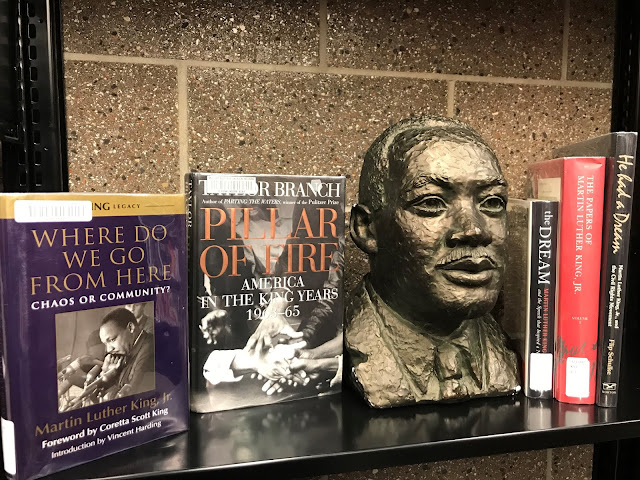 MLK bust posed with 5 books about MLK on a shelf