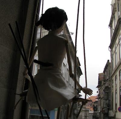 Marioneta numa vitrine em frente a alguns prédios