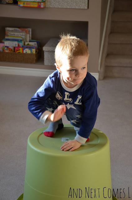 Preschool child slapping simple rhythms on a DIY bucket drum