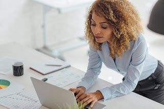 Businesswoman looking at laptop in office