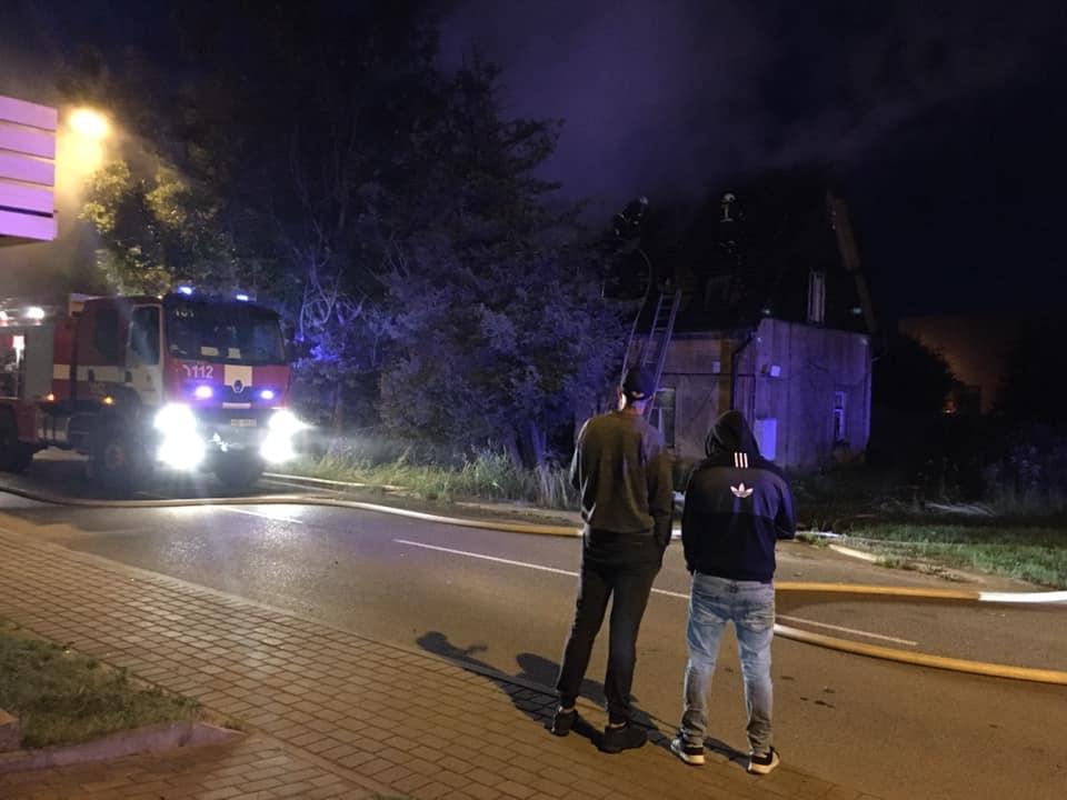 Divi vīrieši vēro ugunsgrēku likvidēšanu