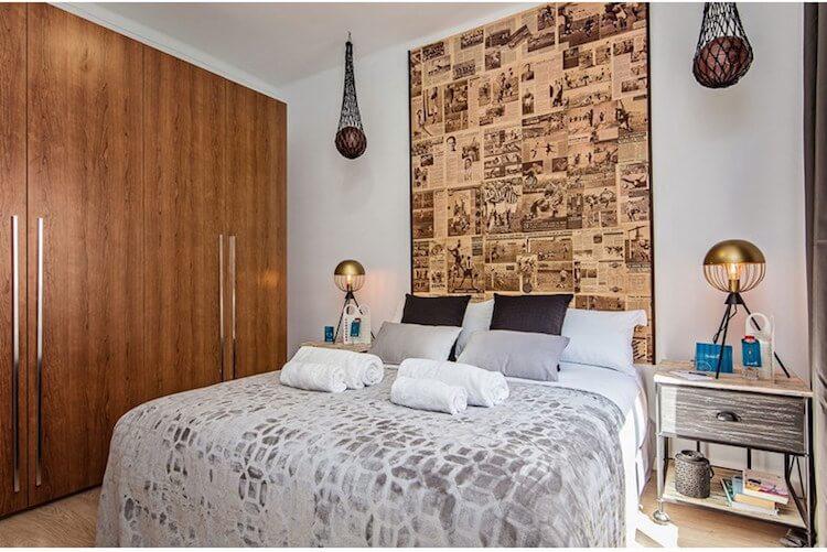 dormitorio con cabecero de recortes de periódico y balones suspendidos