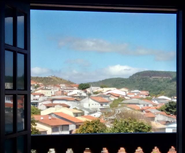 Paisagem de céu, montanha e casario, enquadrados por uma janela.