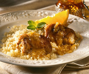 Dish of Chicken over couscous decorated with lemon and mint